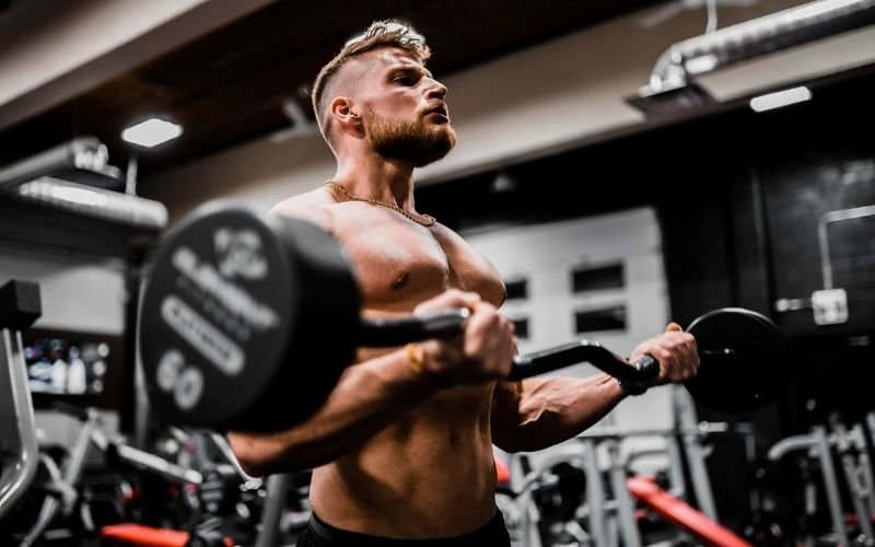 Muscular, shirtless man doing EZ bar bicep curls with 60 pound dumbbell.