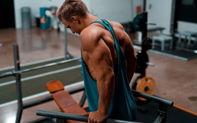 Muscular man in blue tank top doing tricep dips.
