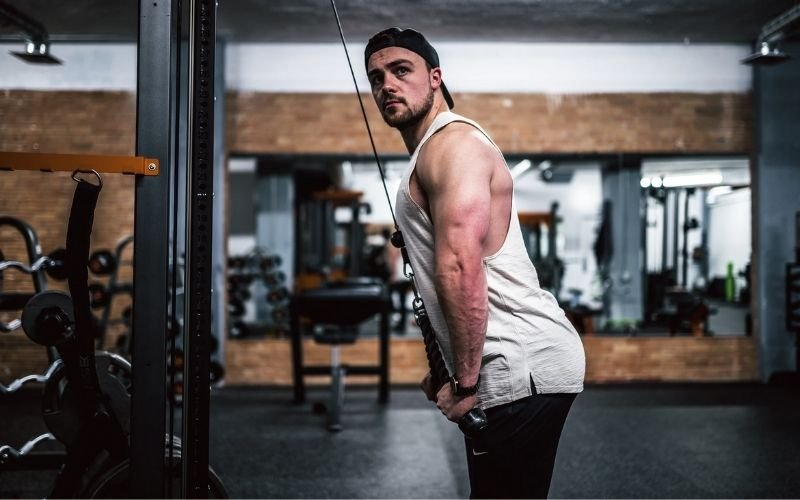 Muscular man in white tank and black backwards hat doing rope tricep pushdowns.