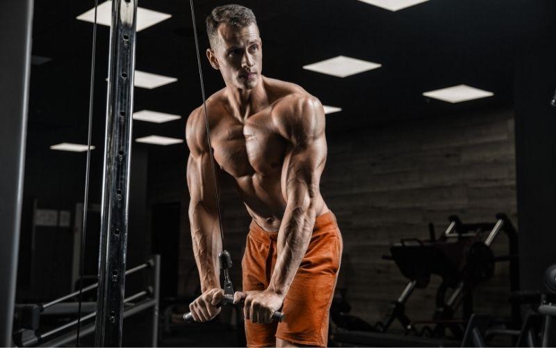 Shirtless man wearing orange shorts doing tricep pushdowns.