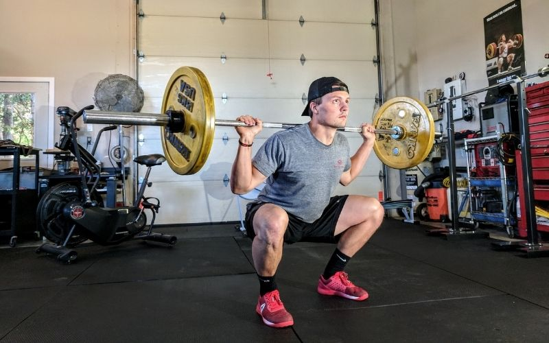 Man in grey t-shirt and black shorts doing a barbell back squat.