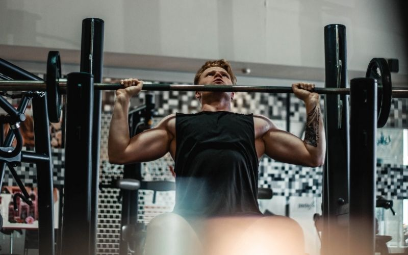 Muscular man in black tank top prepping for seated barbell shoulder press.