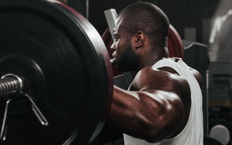 Man wearing white tank standing behind barbell.