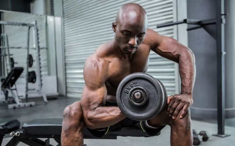 Muscular, shirtless man doing seated bicep curls with 7.5kg dumbbell.