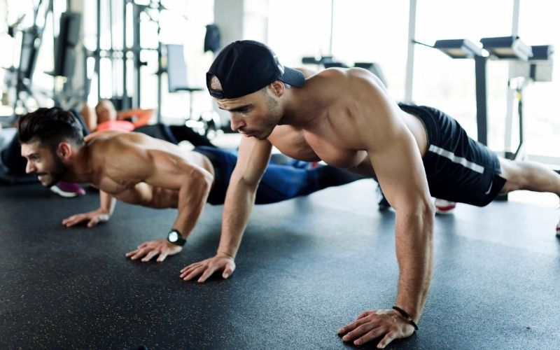 Two men doing push ups in the gym