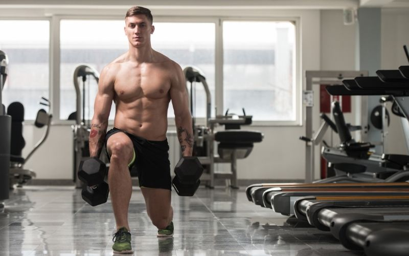 Shirtless man doing lunges holding dumbbells in each hand.