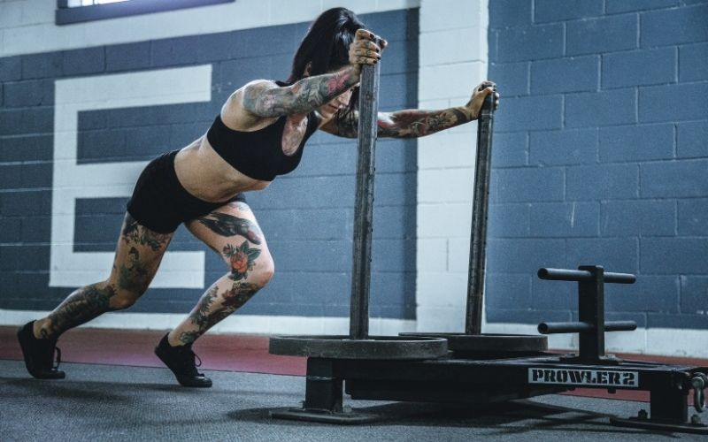 Tattooed muscular woman in black shorts and sports bra pushing a sled.