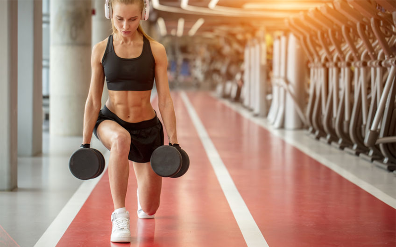 Woman in black sports bra and shorts wearing white headphones doing walking lunges with dumbbells in each hand.