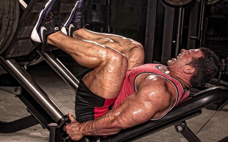 Muscular man doing leg press.