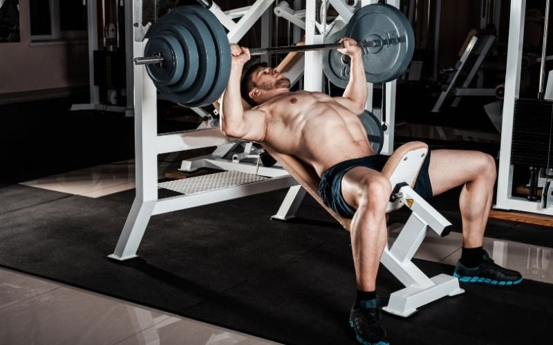 Shirtless male doing incline bench press.