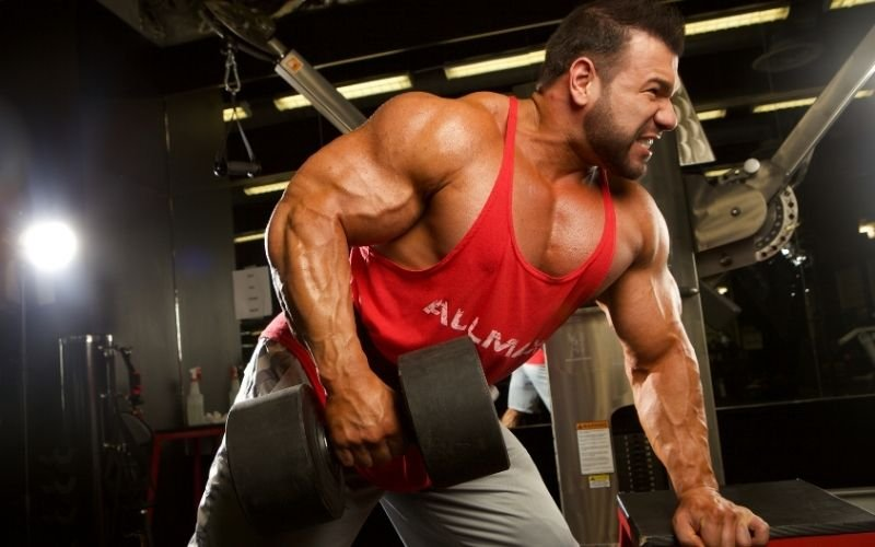 Man in red ALLMAX tank doing single arm dumbbell row.