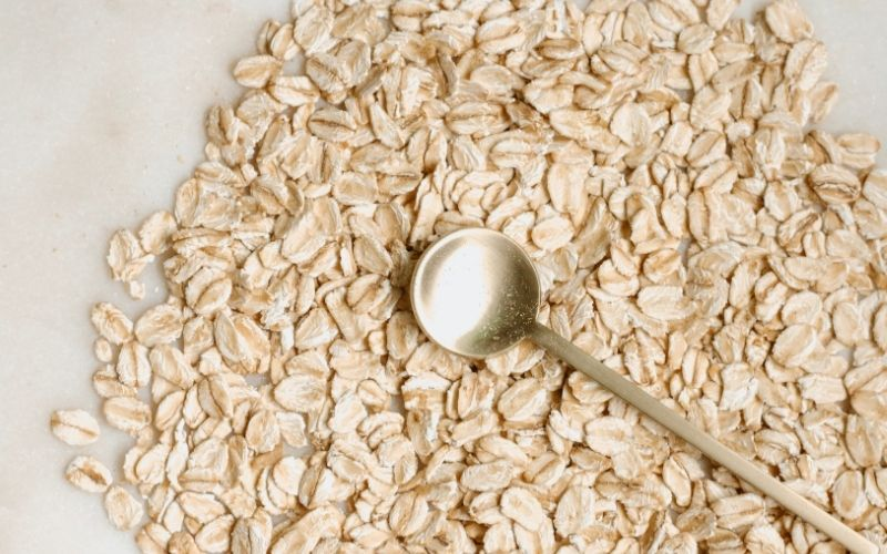 Uncooked oats spread on marble counter with gold spoon on top.