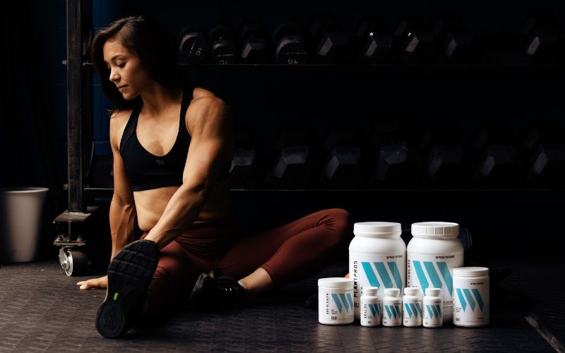 Swolverine athlete stretching next to stack of Swolverine products.