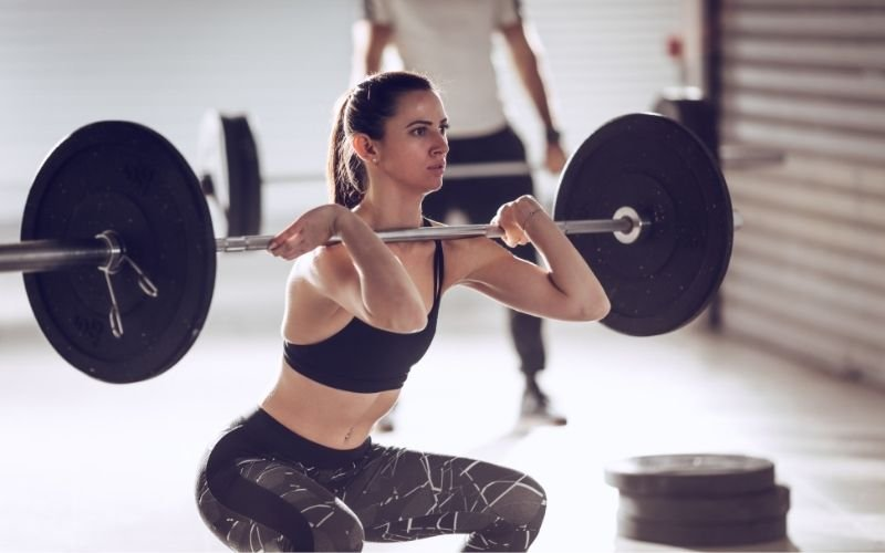 Woman in sports bra and leggings doing barbell front squat.