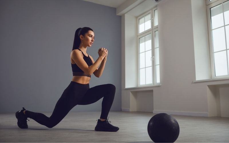 Athletic woman in black sports bra and leggings doing lunges.