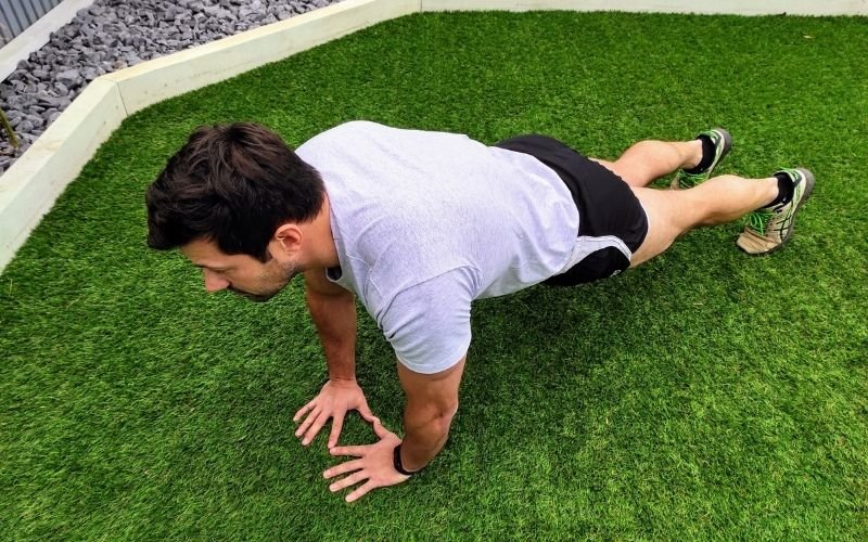 Athletic man doing diamond push up's outside