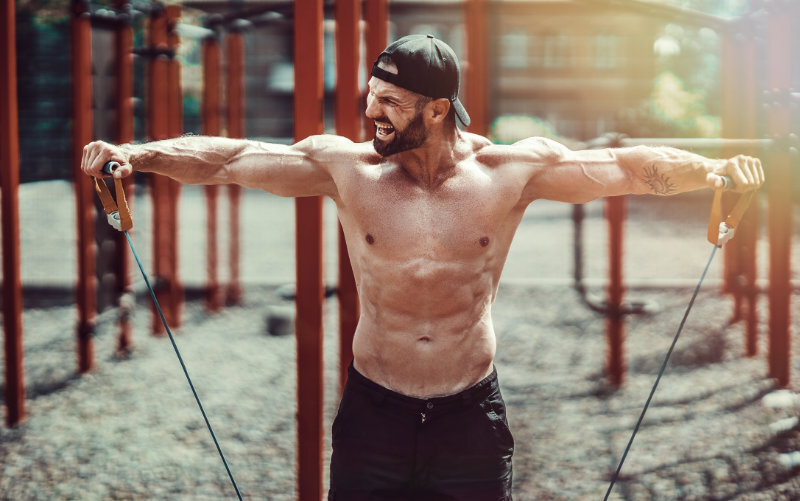 Shirtless man outside doing lateral raises with a resistance band