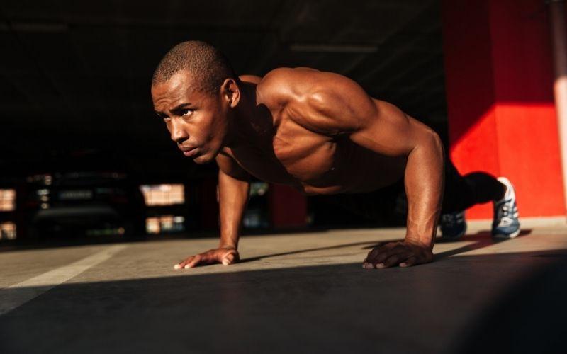 Shirtless muscular man doing pushups.