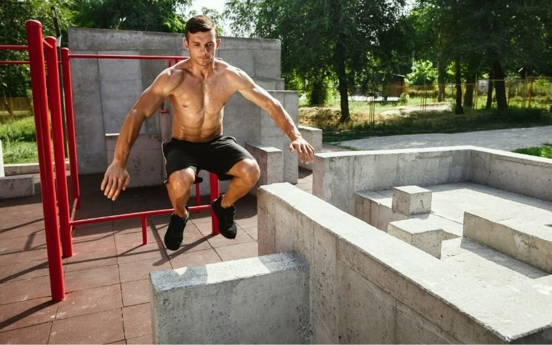 Young and sporty man doing box jumps outdoors