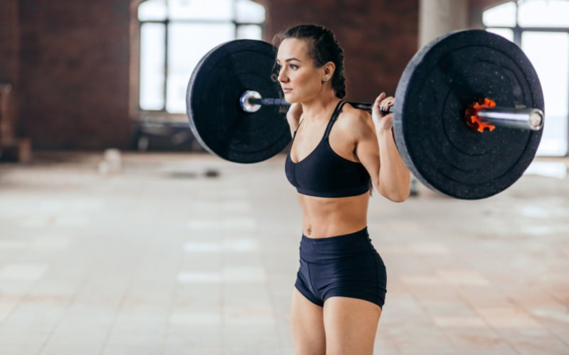 Woman standing with barbell on back in preparation for back squat.