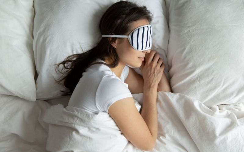 Woman sleeping on her side in bed wearing a striped sleep mask.