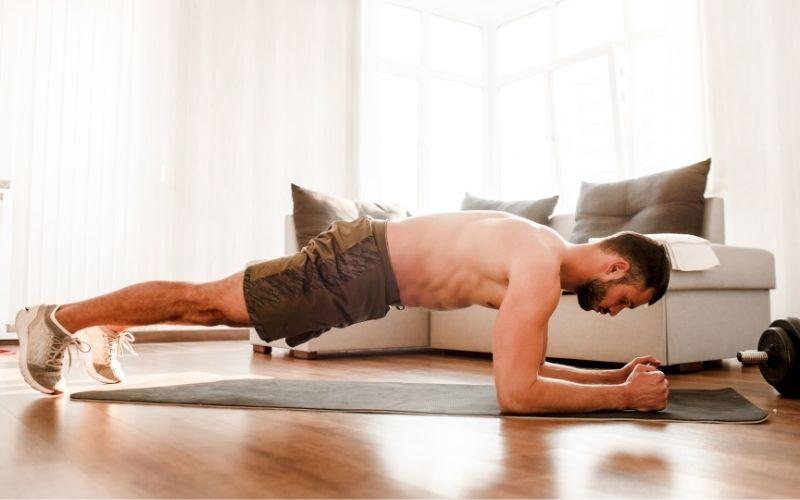 Man doing forearm plank in living room.
