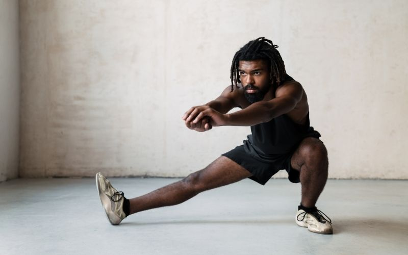 African man doing lateral lunges inside.