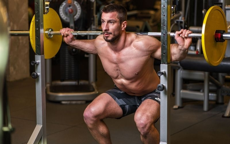 Man doing barbell squat in a gym.