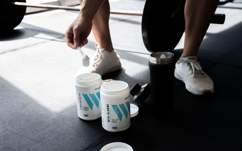 Swolverine athlete scooping beta-alanine and citrulline malate into shaker.