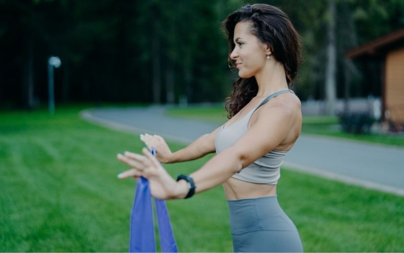 Woman in sports bra and leggings doing band pull-aparts outside.