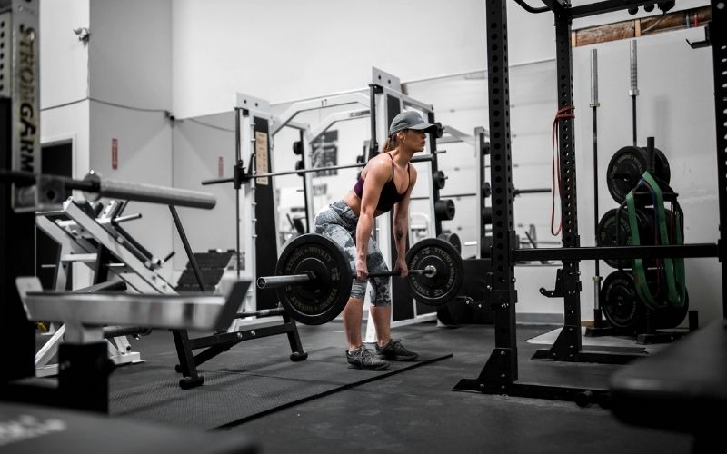 Woman in leggings, sports bra, and hat dong deadlifts in a gym.