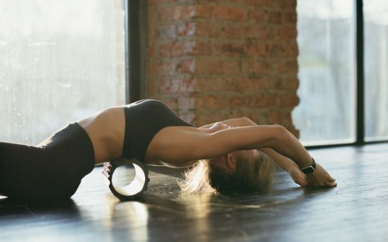 Woman doing foam roller thoracic extensions.