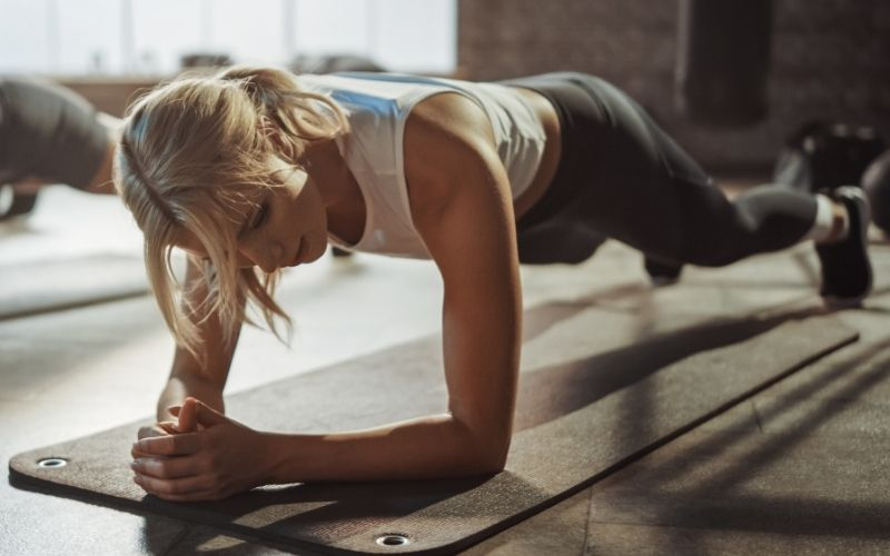 Blonde woman doing forearm plank on yoga mat.