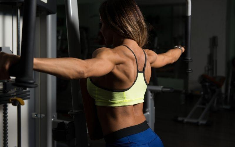 Muscular woman doing machine rear delt flys.