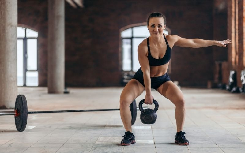 Woman in sports bra and shorts doing single arm kettlebell deadlift inside gym.