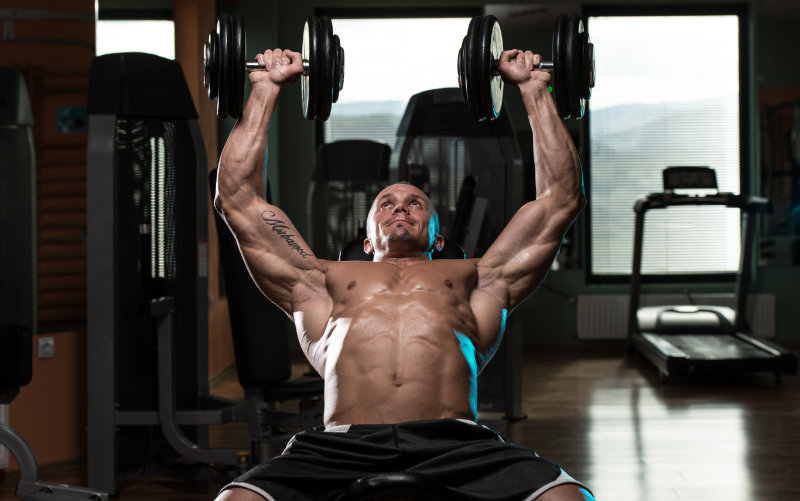 Shirtless man doing incline bench press in a commercial gym.