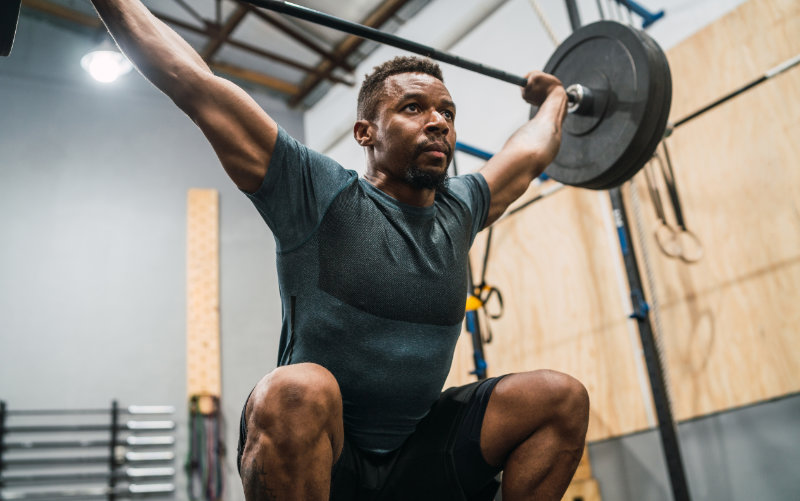 Man in the receiving position of a squat snatch in a CrossFit style gym.