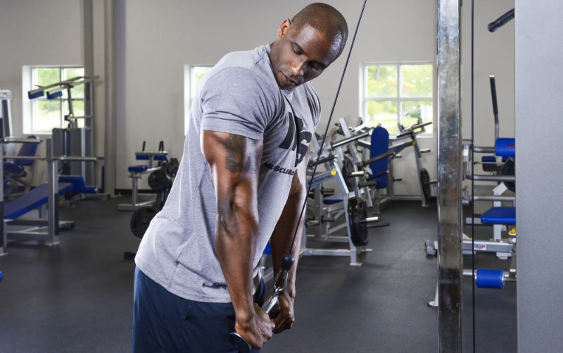Muscle & Strength model wearing grey M&S t-shirt doing cable tricep pushdowns.