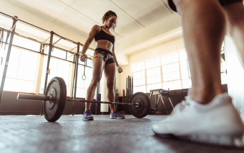 Woman prepping for deadlifts in a CrossFit-style gym.