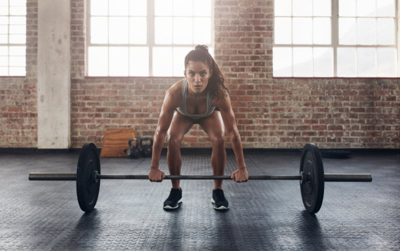 Woman doing deadlifts in CrossFit-style gym.
