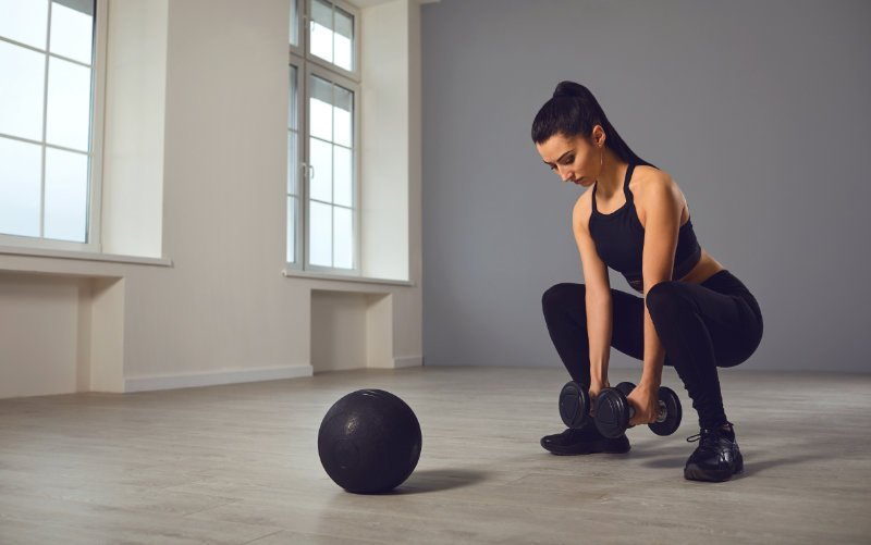 Woman doing dumbbell squats in studio gym with wall ball on the ground in front of her.
