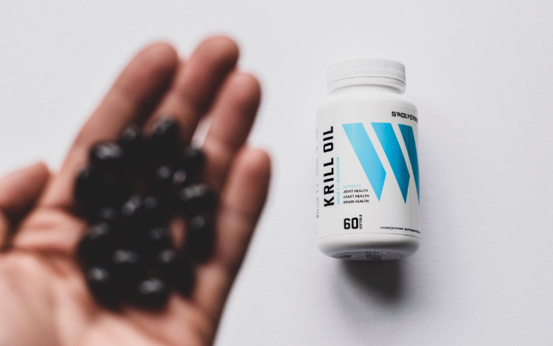 Top-down image of a hand full of black pills in front of a bottle of Swolverine krill oil.