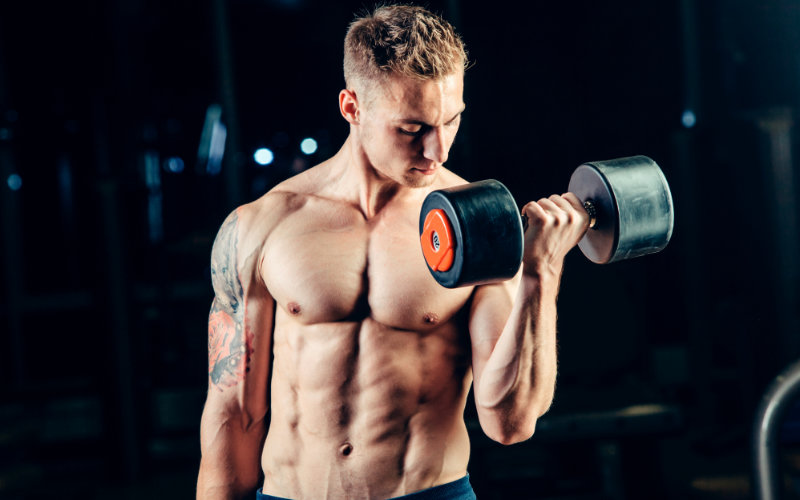 Muscular shirtless man doing dumbbell curls in gym setting.