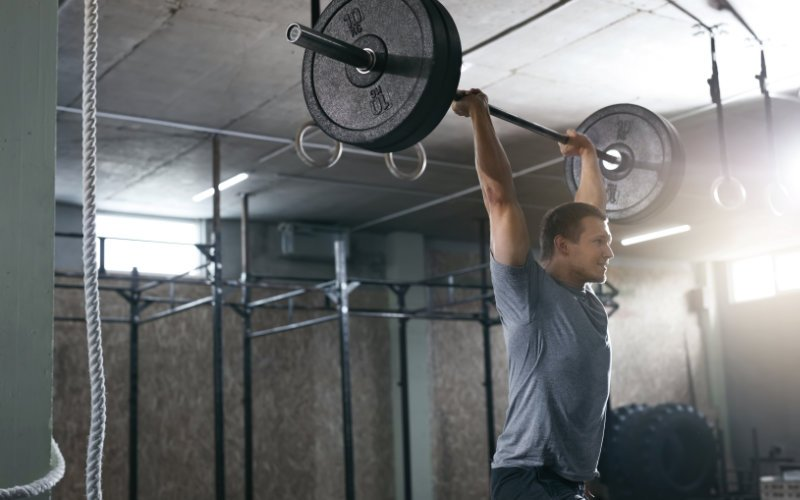 Man in the overhead position of a jerk in a CrossFit-style gym.