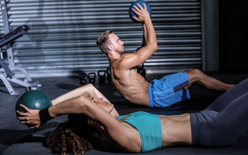 Man and woman doing medicine ball sit ups in gym setting.