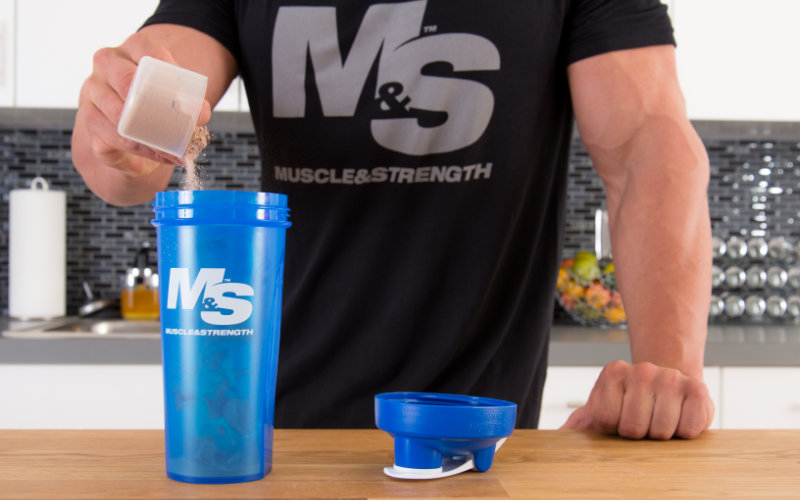 M&S model pouring scoop of protein powder into blue M&S shaker in a kitchen.
