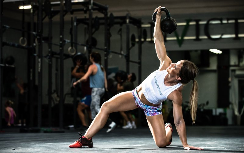 Swolverine athlete performing a Turkish get up in CrossFit-style gym.