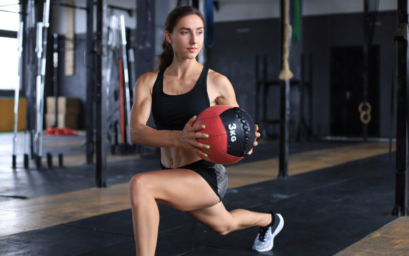 Woman doing luges with medicine ball in Crossfit-style gym.