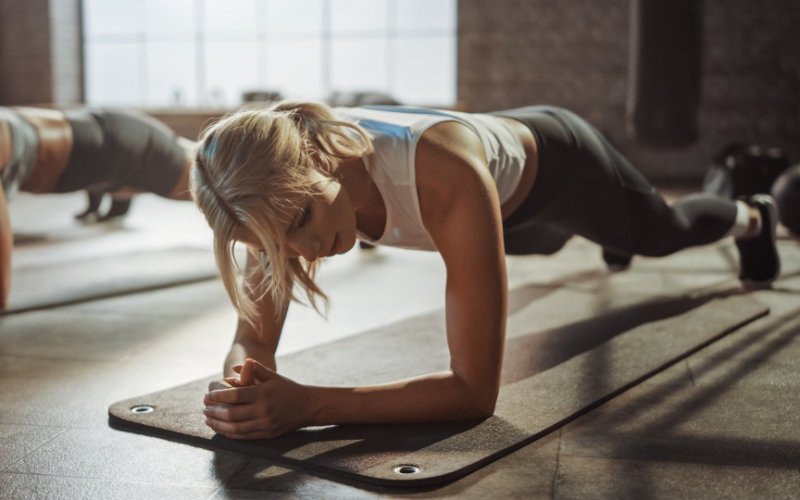 Blonde woman doing planks in a fitness studio.