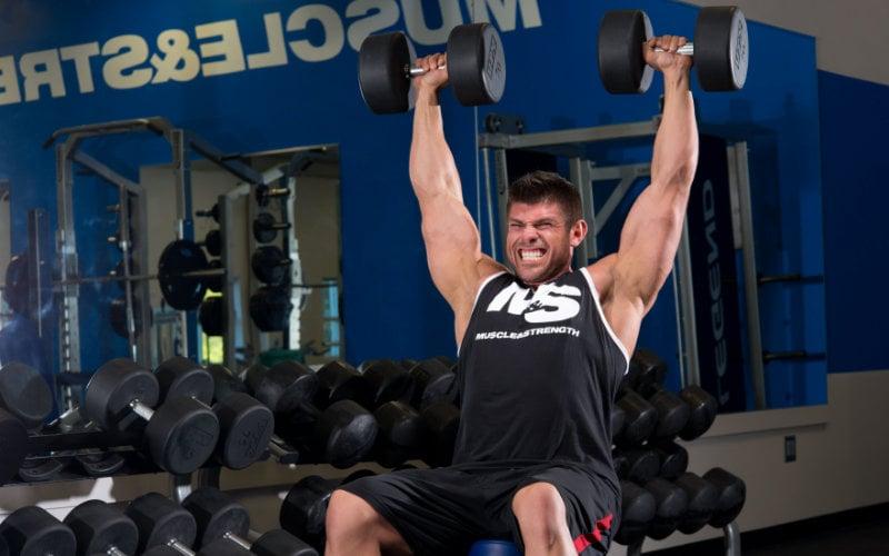 M&S model doing dumbbell shoulder press in gym.